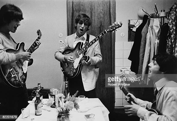 George Harrison John Lennon and Paul McCartney of the Beatles tuning up backstage before a concert at the Ernst Merck Halle Hamburg during their last...