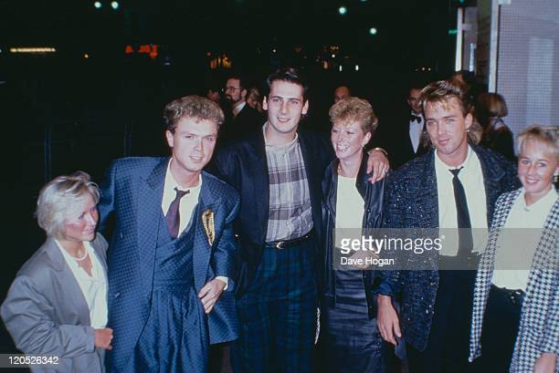 Left to right guitarist Gary Kemp singer Tony Hadley and bassist Martin Kemp of British pop group Spandau Ballet with their partners 1984 Hadley is...