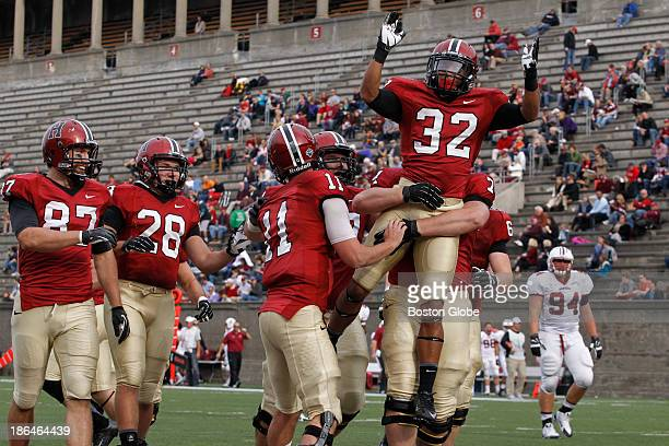 Left to right Harvard Crimson's tight end Cameron Brate running back Andrew Casten celebrate as quarterback Michael Pruneau offensive lineman Nick...