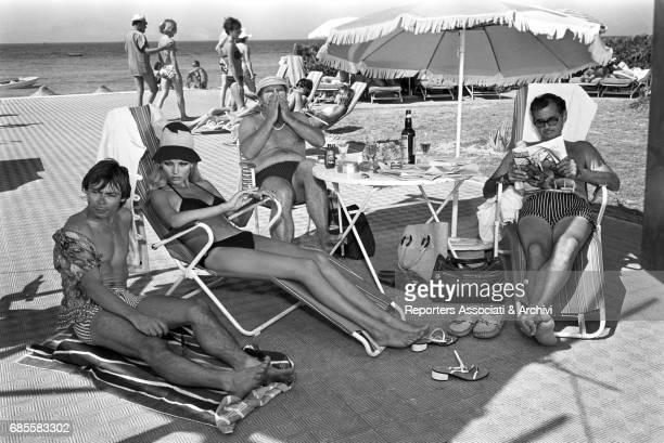 italian actor Claudio Trionfi swedish actress Janet Agren american actors Eugene Walter Jeff Morrow relaxing under the beach umbrela in the film...