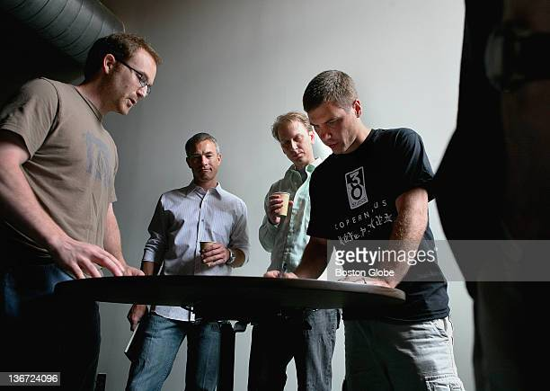 Left to right Jason Armstrong President and CEO Brett Close Aaron Carlson and Brian Labore take part in a daily scrum at 38 Studios in Maynard...