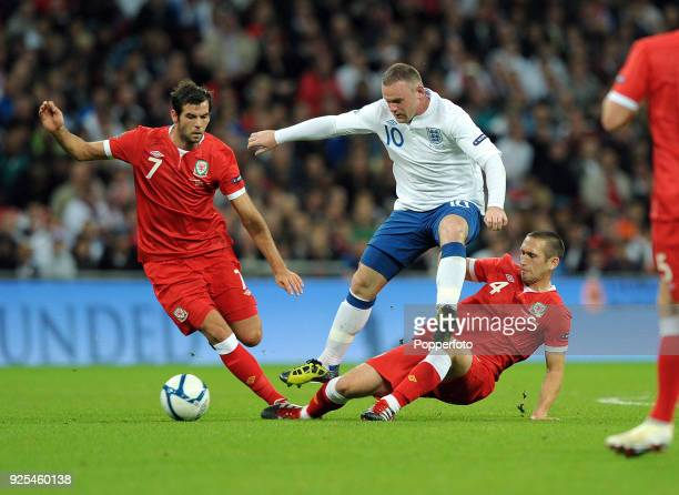 Left to right Joe Ledley of Wales Wayne Rooney of England and Andrew Crofts of Wales in action during the UEFA EURO 2012 group G qualifying match...