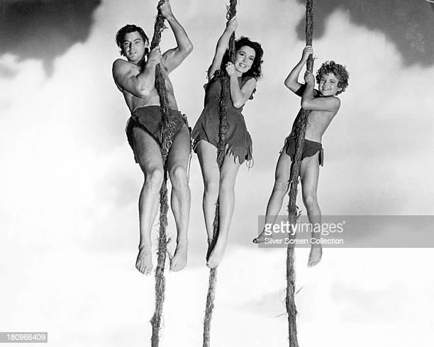 Johnny Weissmuller as Tarzan Maureen O'Sullivan as Jane Parker and Johnny Sheffield as Boy swinging on vines in a promotional still for 'Tarzan's...