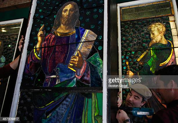 Left to right Kyle Wallace and John Kenyon of Kingston RI work to install a stain glass panel of Jesus at the Cyclorama in Boston Massachusetts...