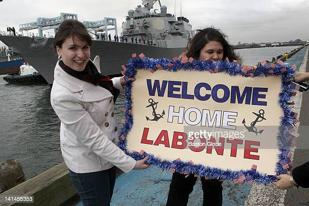 Left to right Natile Silver holds a sign that welcomes her fiancee petty officer Keenan Labonte with help from his sister Jenna Labonte and his...