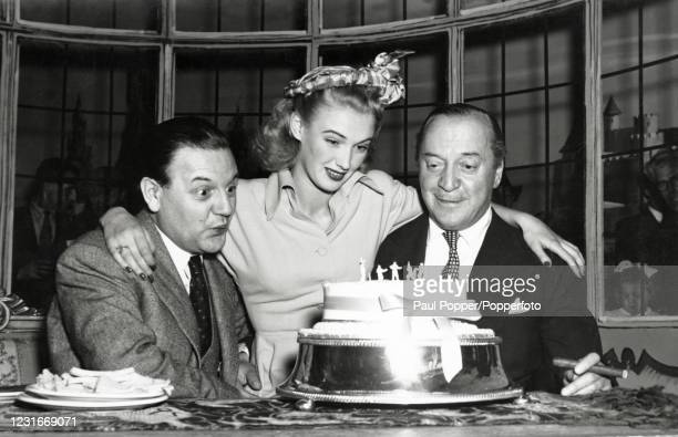 "Left to right, Naunton Wayne, Susan Shaw and Basil Radford, English actors, on the set of the film ""It's Not Cricket"", circa 1949."