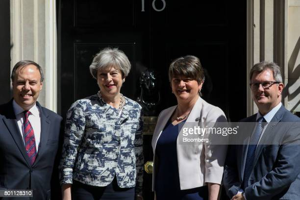 Left to right Nigel Dodds deputy leader of the Democratic Unionist Party Theresa May UK prime minister Arlene Foster leader of the Democratic...
