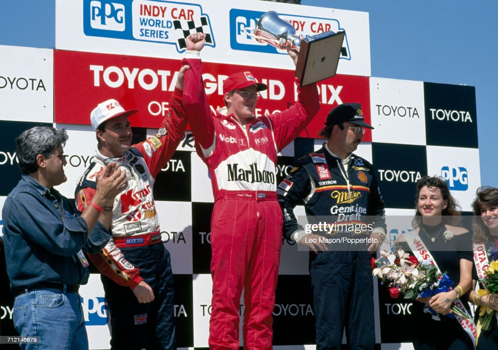 Nigel Mansell of Great Britain (third), Paul Tracy of Canada with the trophy (first) and Bobby Rahal of the United States (second) stand together on the victory podium following the IndyCar Streets of Long Beach Grand Prix in Long Beach, United States on 18th April 1993. American television host and comedian Jay Leno stands on far left.
