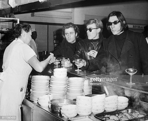 Left to right Poet Gerard Malanga artistmoviemaker Andy Warhol and avantgarde musician John Cale at the champagne breakfast held at the Automat...