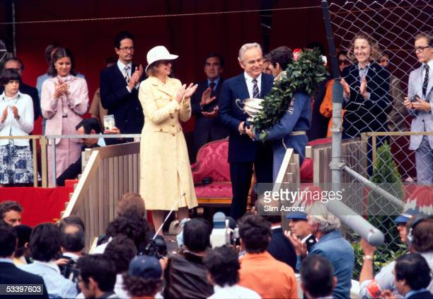 princesses Stephanie Caroline and Grace of Monaco applaud as Prince Rainier III presents a trophy to South African racing driver Jody Scheckter after...