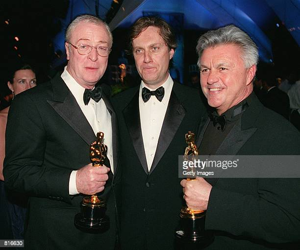 Left to right recipient of Best Supporting Actor Michael Caine director Lasse Hallstrom and John Irvin recipients for Best Screen Play for the film...