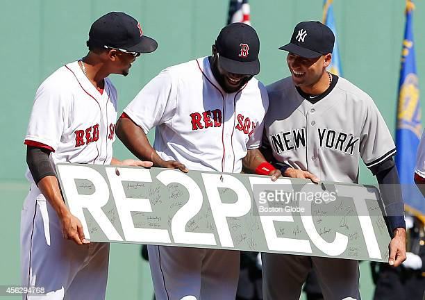 Left to right Red Sox Xander Bogaerts and David Ortiz present Yankees Derek Jeter with a sign reading 'RE2PECT' as the Red Sox pay tribute to Derek...