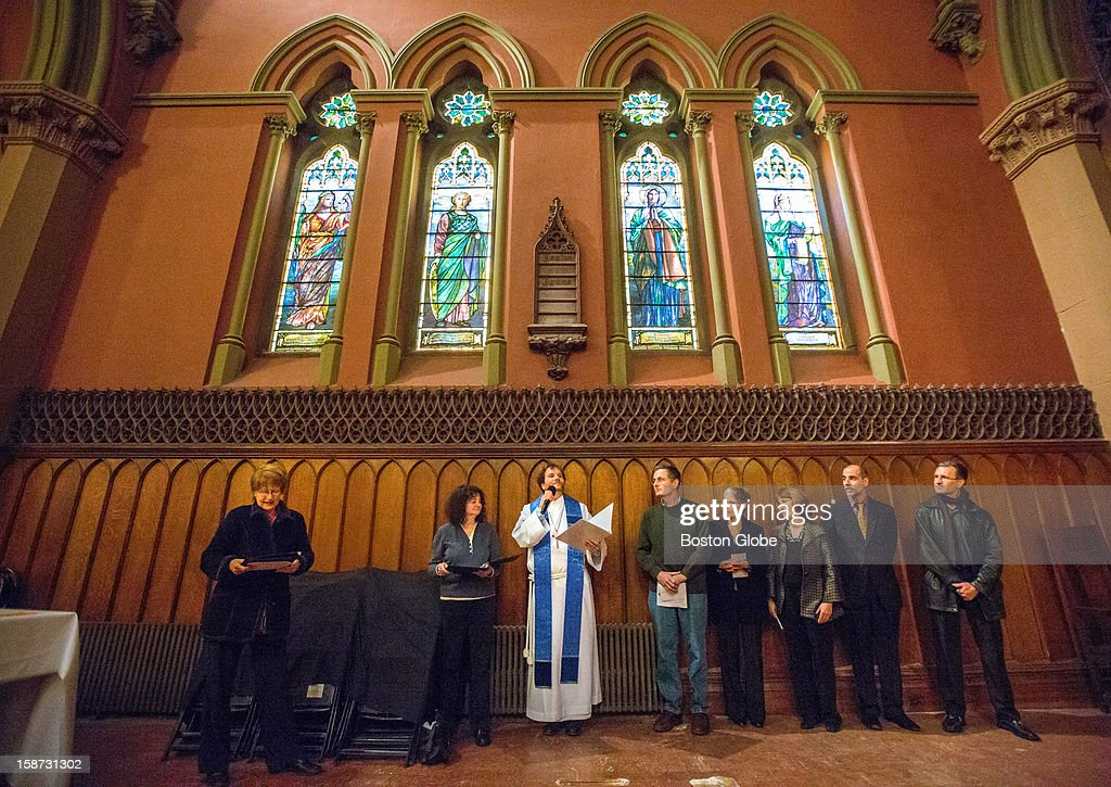 Left to right, Reverend Rob Mark, center, spoke during the rededication of the 'Dorcas Window,' top right, at the Church of the Covenant on Newbury Street in Boston. Part of the stained glass window was shattered during a break-in last year.