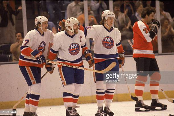 Teammates Stefan Persson, Denis Potvin and Mike Bossy of the New York Islanders celebrate a goal as Bob Dailey of the Philadelphia Flyers skates past...
