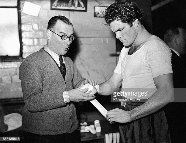 Left to right trainer Nat Seller tapes Freddie Mills' hands before a sparring session