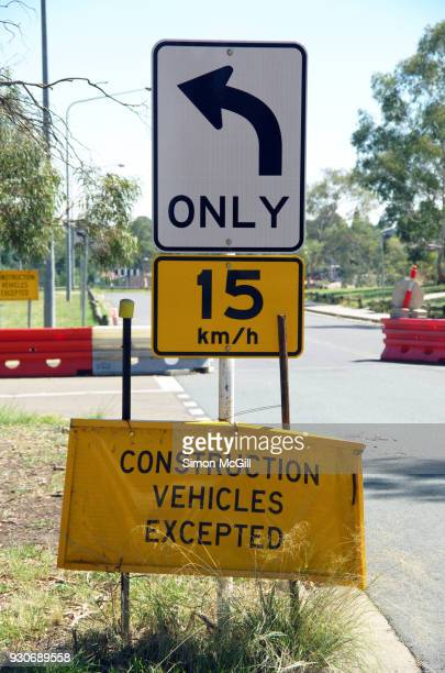 Left Turn Only, 15 kilometre per hour speed limit, and Construction Vehicles Excepted signs near a road into a construction site