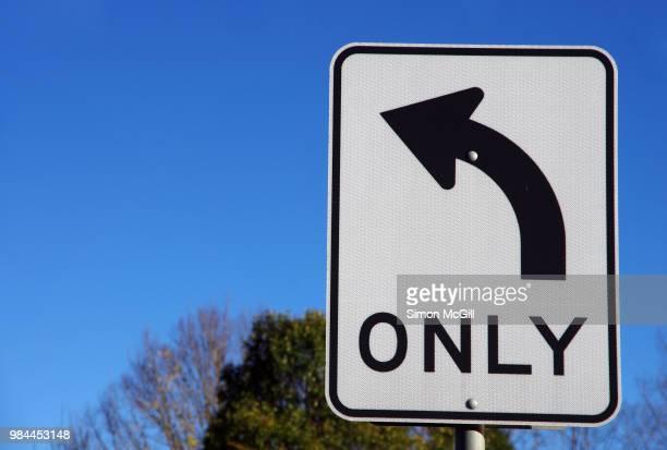 'left turn only' road sign - curved arrows - fotografias e filmes do acervo