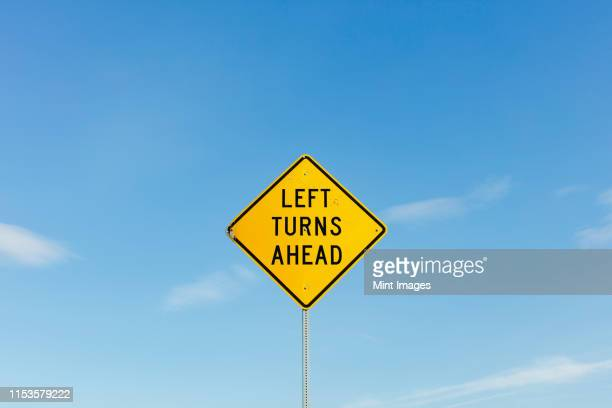 left turns ahead yellow traffic sign - road sign stock pictures, royalty-free photos & images