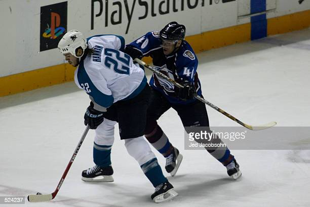 Left wing Alex Tanguay of the Colorado Avalanche pressures defenseman Scott Hannan of the San Jose Sharks during game three of the Stanley Cup...