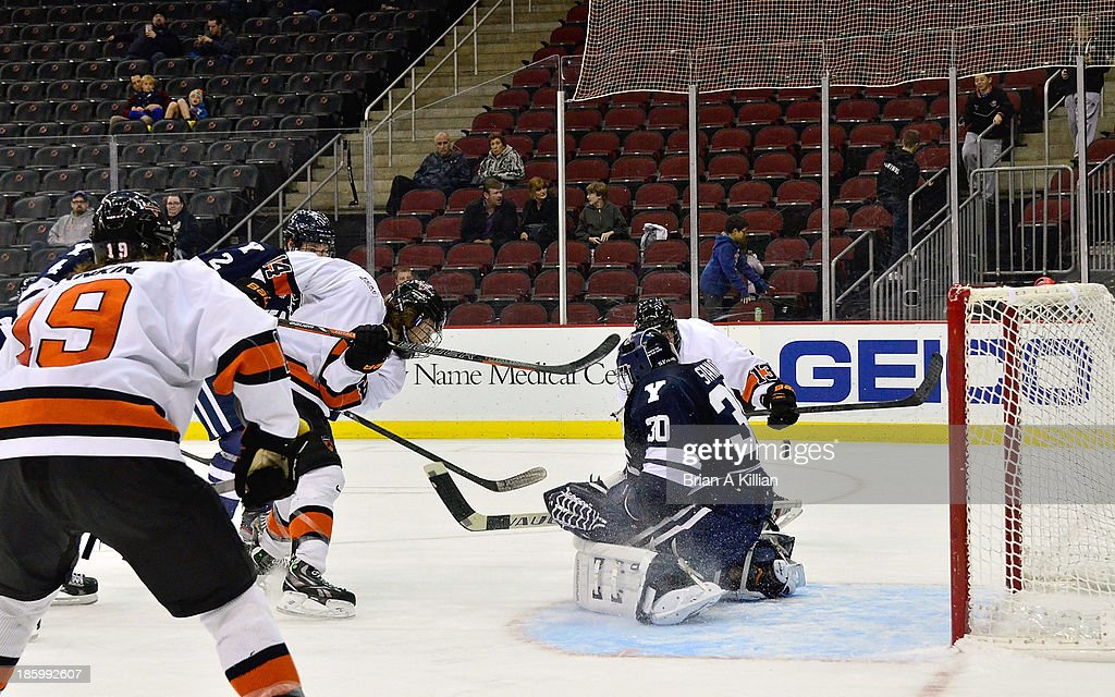 Left wing Andrew Ammon #14 of the Princeton Tigers scores a goal against goalie Patrick Spano #30 of the Yale Bulldogs at Prudential Center on October 26, 2013 in Newark, New Jersey. The Yale Bulldogs defeated the Princeton Tigers, 3-2.