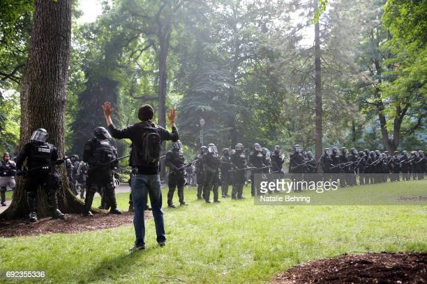Left wing 'Antifa' protester holds up his hands as police seek to clear a park at a rally on June 4, 2017 in Portland, Oregon. A protest dubbed...