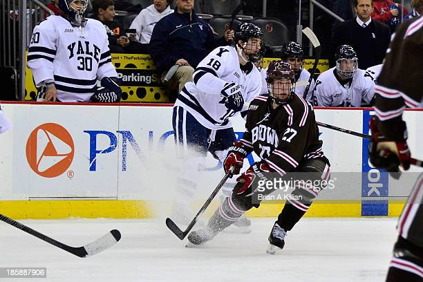 Left wing Kenny Agostino of the Yale Bulldogs and center Mark Naclerio of the Brown Bears compete for the puck at Prudential Center on October 25...