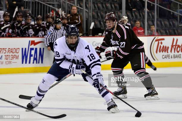 Left wing Kenny Agostino of the Yale Bulldogs looks to shoot the puck as center Mark Naclerio of the Brown Bears attacks from behind at Prudential...
