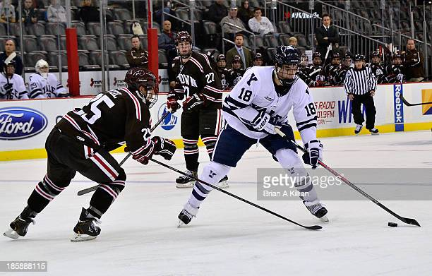 Left wing Kenny Agostino of the Yale Bulldogs tries to shoot the puck as defenseman Brandon Pfeil of the Brown Bears defends at Prudential Center on...