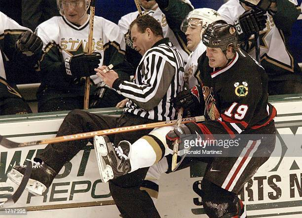 Left wing Kyle Calder of the Chicago Blackhawks checks Stephane Robidas of the Dallas Stars into linesman Randy Mitton at the American Airlines...