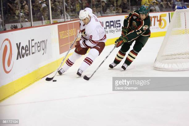 Left wing Mike Leclerc of the Phoenix Coyotes skates with the puck against defenseman Willie Mitchell of the Minnesota Wild at Xcel Energy Center on...