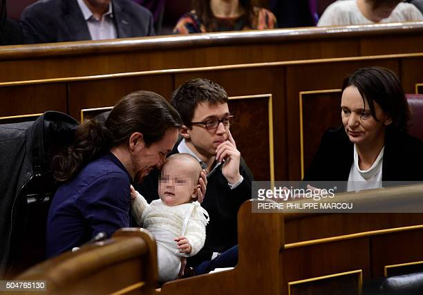 Left wing party Podemos' leader Pablo Iglesias plays with the baby of Podemos' deputy Carolina Bescansa past Podemos' member Inigo Errejon during the...