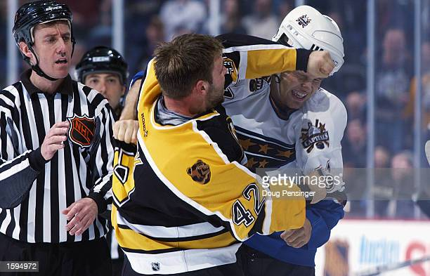 Left wing PJ Stock of the Boston Bruins throws a punch at right wing Stephen Peat of the Washington Capitals as linesman Pat Dapuzzo watches in the...