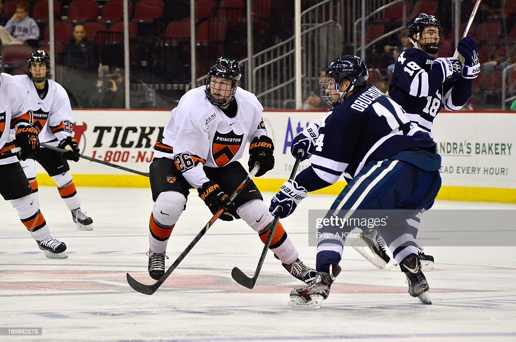 Left wing Ryan Siiro #26 of the Princeton Tigers tries to skate past defenseman Ryan Obuchowski #14 of the Yale Bulldogs at Prudential Center on October 26, 2013 in Newark, New Jersey. The Yale Bulldogs defeated the Princeton Tigers, 3-2.