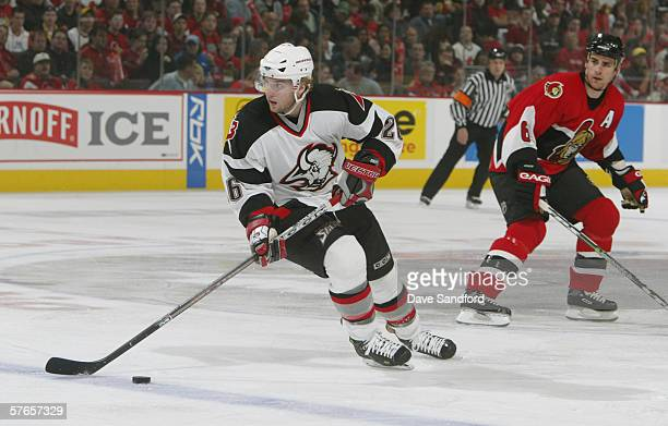 Left wing Thomas Vanek of the Buffalo Sabres plays the puck as defenseman Wade Redden of the Ottawa Senators looks on in game one of the Eastern...