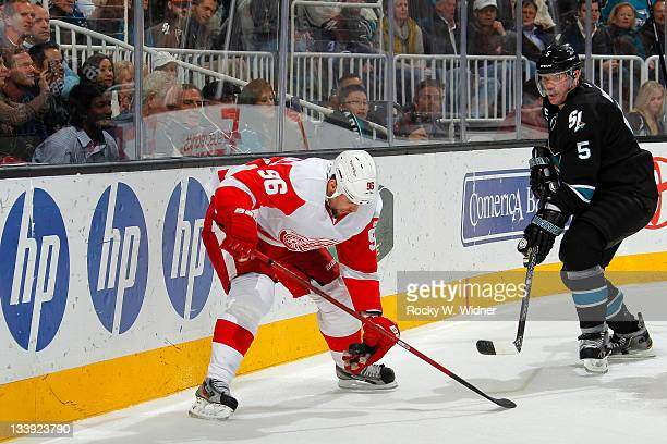 Left wing Tomas Holmstrom of the Detroit Red Wings settles the puck with his hand against defenseman Colin White of the San Jose Sharks at the HP...
