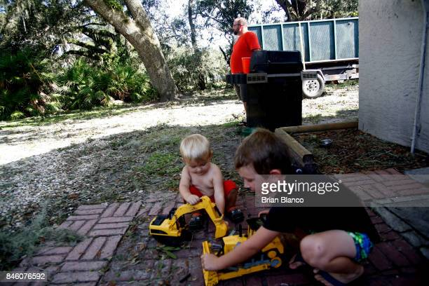 Left without power to his home David Osteen grills lunch for his family as his children Liam and Landry play outside with toys in the wake of...