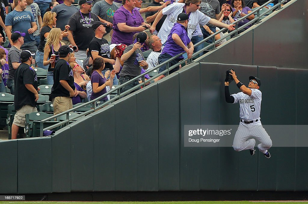 Leftfielder Carlos Gonzalez #5 of the Colorado Rockies leaps against the wall to catch a foul ball for an out on Carlos Quentin #18 of the San Diego Padres in the first inning during Opening Day at Coors Field on April 5, 2013 in Denver, Colorado.