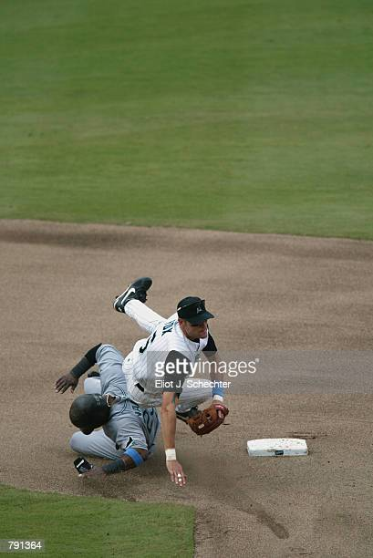 Leftfielder Greg Vaughn of the Tampa Bay Devil Rays takes out shortstop Andy Fox of the Florida Marlins after he throws to first base during the MLB...