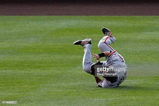 Leftfielder Nori Aoki of the San Francisco Giants rolls as he makes a catch on a line drive by Brandon Barnes of the Colorado Rockies in the fifth...