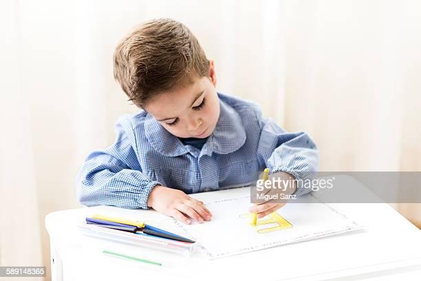 Left-handed boy sitting at desk doing homework