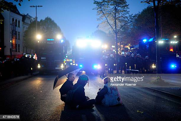 Leftist activists sit in front of water cannons after clashing with riot police during annual May Day demonstrations on May 1, 2015 in Hamburg,...