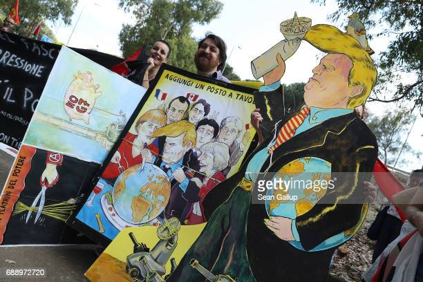 Leftist demonstrators including one carrying a coardboard effigy of US President Donald Trump and another showing the heads of state of the G7...
