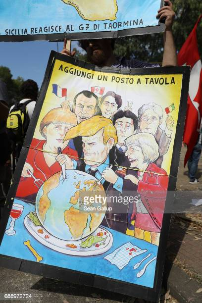 Leftist demonstrators including one carrying a handpainted poster showing the heads of state of the G7 nations feasting on the planet Earth prepare...