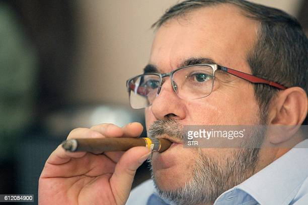 FARC leftist guerrilla commander Timochenko smokes a cigar while watching on TV the results of a referendum on wether to ratify a peace accord to end...