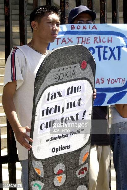 A leftist protester holds a mobile phone dummy as he and others stage a rally near the gate of Finance building in Manila 20 december 2002 to oppose...