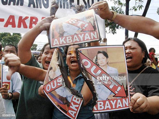 Leftist protesters burn portraits of Philippine president Gloria Arroyo at a protest outside the House of Representative in Manila 31 August 2005...