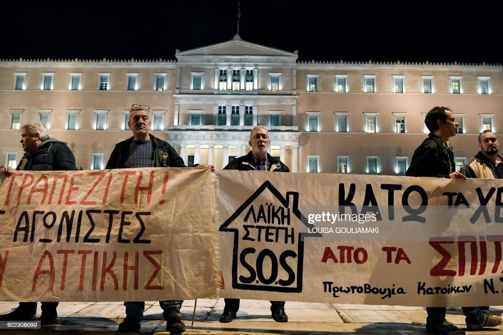 Leftist protesters hold a banner that reads 'not a house in the hands of a banker' in front of the Greek parliament in central Athens on February 21, 2018 during a demonstration against property auctions demanded by Greece's creditors as part of the Greek austerity measures. Forced auctions of properties are seen as essential to restore Greece's banking system by its lenders. /