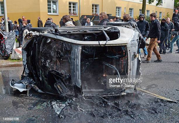 Leftist protesters walk past a burned out car during a march by neo-Nazis on June 2, 2012 in Hamburg, Germany. Thousands of protesters took to the...