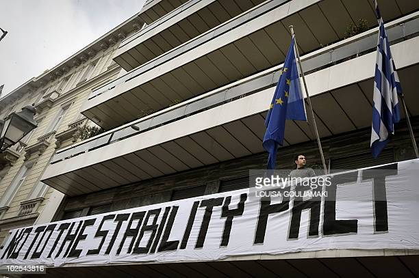 A leftist protestor stands by a banner hung on a balcony of the EU central office in Athens on February 23 2010 Protestors hung the banner to...