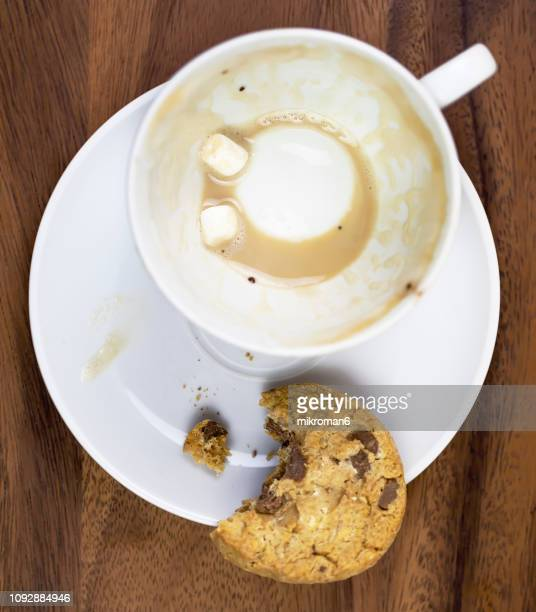 Leftovers In Coffee Cup with Bitten Biscuit